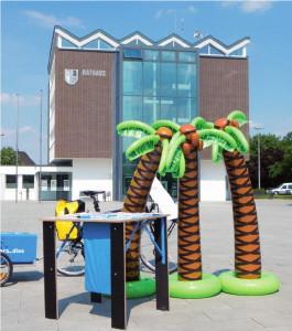 Drei Palmen, hier vor dem Rathaus in Weeze, verdeutlichten: Das Paradies ist vielleicht gar nicht so weit weg.