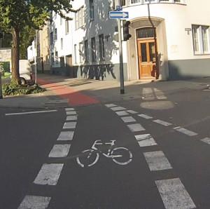 Sonstiger Radweg mit Bodenpiktogramm und roter Flächenmarkierung