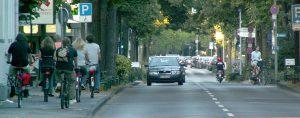Dorfstraße: Radfahrer flüchten vor den Autos auf den Gehweg. Sie müssen durch eine fahrradfreundliche Verkehrsführung wieder auf die Fahrbahn geholt werden.